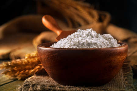 Flour in a bowl with a flour spoon, on a rustic wooden background. Close up, side view, high-resolution product image. Standard-Bild