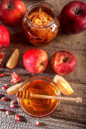 Jewish holiday Rosh Hashanah. Apples, pomegranate and honey on the rustic wooden table. Vintage style composition on a rustic wooden background. Standard-Bild