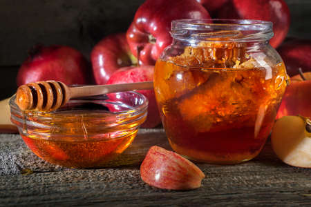 Jewish holiday Rosh Hashanah. Apples and honey on the rustic wooden table. Vintage style composition on a rustic wooden background.