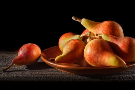 Fresh pears on the plate. Old rustic table. Pears harvest. Fresh organic fruits, selective focus. Juicy flavorful pears in wooden plate. Autumn nature concept.