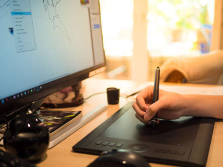 closeup hand of a boy Drawing tablet and Pen on a computer