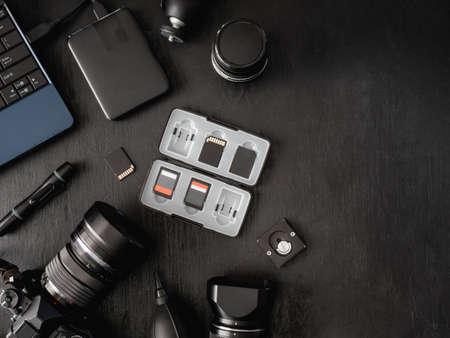 vista dall'alto dello spazio di lavoro fotografo con fotocamera digitale, flash, kit di pulizia, scheda di memoria, disco rigido esterno, lettore di schede USB, laptop e accessorio per fotocamera su sfondo nero Archivio Fotografico