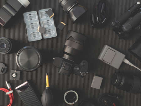 top view of work space photographer with digital camera, flash, cleaning kit, memory card and camera accessory on black table background.