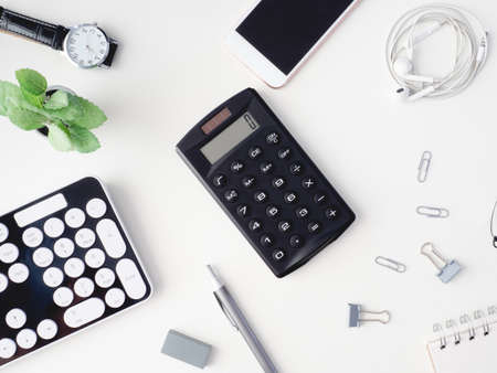 top view of office desk table with notebook, calculator, plastic plant, smartphone and keyboard on white background, graphic designer, Creative Designer concept. Reklamní fotografie