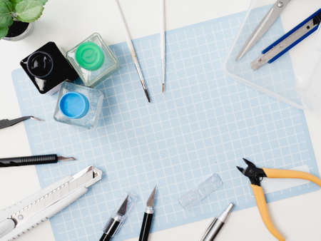 top view of hobbies concept with cutting mat and tool kits on white background with copy space.