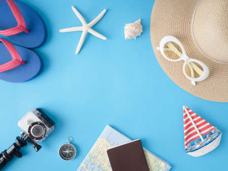 top view travel concept with action camera, map, passport, smartphone and Straw Hat on blue background with copy space, Tourist essentials, vintage tone effect Reklamní fotografie
