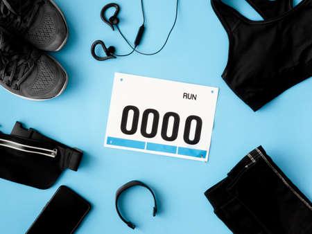 俯视图的跑步活动概念与跑步鞋,号码布和跑步配件在蓝色背景。