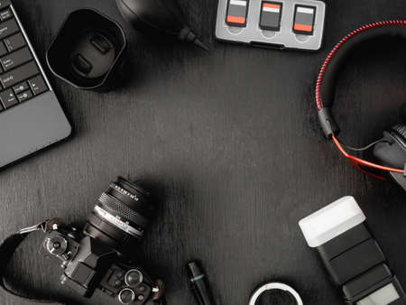 top view of work space photographer with digital camera, flash, cleaning kit, memory card, external harddisk, USB card reader, laptop and camera accessory on black table background Reklamní fotografie