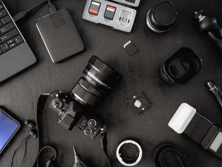 Draufsicht des Arbeitsplatzfotografen mit Digitalkamera, Blitz, Reinigungsset, Speicherkarte, externer Festplatte, USB-Kartenleser, Laptop und Kamerazubehör auf schwarzem Tischhintergrund