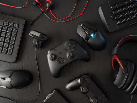 gamer workspace concept, top view a gaming gear, mouse, keyboard, joystick, headset, mobile joystick, in ear headphone and mouse pad on black table background with copy space. Reklamní fotografie