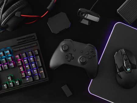 koncepcja przestrzeni roboczej gracza, widok z góry sprzęt do gier, mysz, klawiatura, joystick, zestaw słuchawkowy i podkładka pod mysz na tle białego stołu.