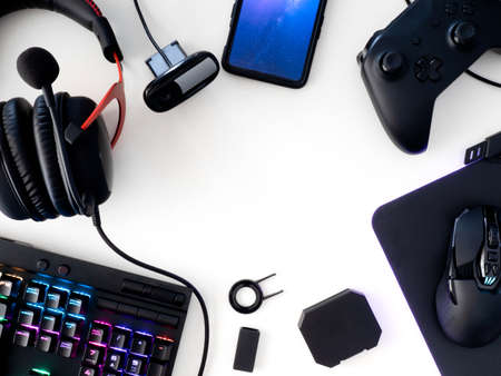 streaming games concept, top view a gaming gear, mouse, Webcams, keyboard, joystick, headset and mouse pad on white table background.