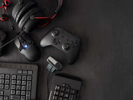 Gamer-Arbeitsplatzkonzept, Draufsicht auf Gaming-Ausrüstung, Maus, Tastatur, Joystick, Headset, mobiler Joystick, In-Ear-Kopfhörer und Mauspad auf schwarzem Tischhintergrund.