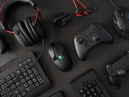 gamer work space concept, top view a gaming gear, mouse, keyboard, joystick, headset, mobile joystick, in ear headphone and mouse pad on black table background. Stock Photo
