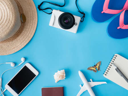 top view travel concept with digital camera, smartphone, map, passport, compass and Outfit of traveler on blue background, Tourist essentials, vintage tone effect Reklamní fotografie