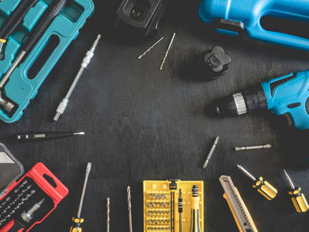 top view of Construction tools concept with Drill sets, hammer, screwdriver and Toolbox on black wooden background. Reklamní fotografie