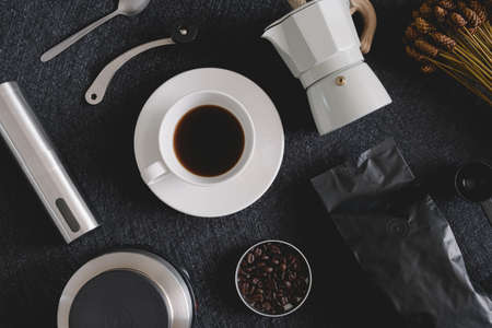 coffee cup and moka pot on black table background in kitchen room, coffee shop.