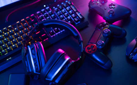 gamer work space concept, top view a gaming gear, mouse, keyboard, joystick, headset with rgb color on black table background. Banque d'images