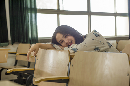 collegian: Beautiful Asian college student in classroom