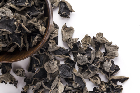 cloud ear fungus: Dried black fungus in a wooden bowl  on the white background