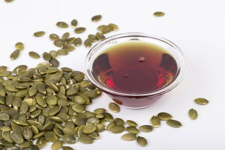 Pumpkin seed oil and seeds on the white