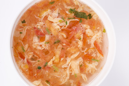 Egg soup with tomatoes in a bowl.