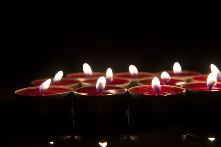 Burning candle isolated on black background. Imagens