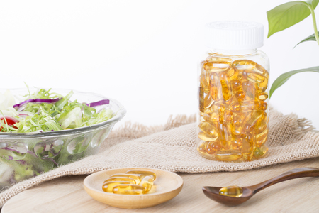 longevity drugs: Healthy life, Fish oil capsules and salad on the table Stock Photo