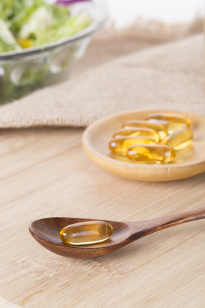 Fish oil capsules and salad on the table Stock Photo