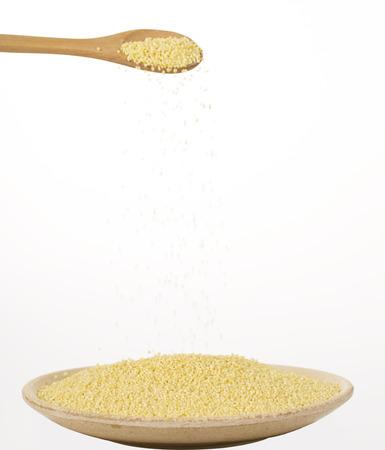 sorgo: Semillas de mijo amarillo cayendo de una cuchara Foto de archivo