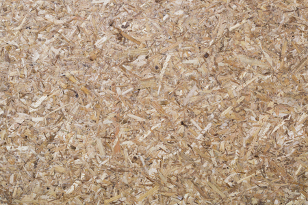 Oriented Strand Board. Wooden panel made of pressed of sandy brown wood shavings as background closeup.