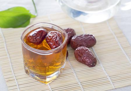 中国の赤い日付ティー テーブルの上のガラスのコップ。中国の赤い日付は、赤色の血液細胞の生産を促進するのに役立つ栄養補助食品と考えられて 写真素材