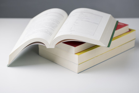 Pile of books with one book open on white table. Stock Photo