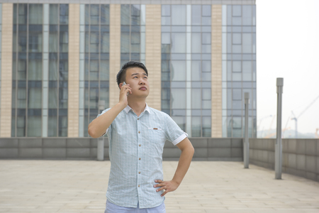 Young man using a mobile phone standing outside a modern office building.