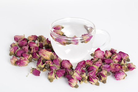 tea hot drink: A cup of rose tea with dried rose flower on white background.