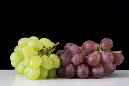Fresh grapes on a white table and black background.