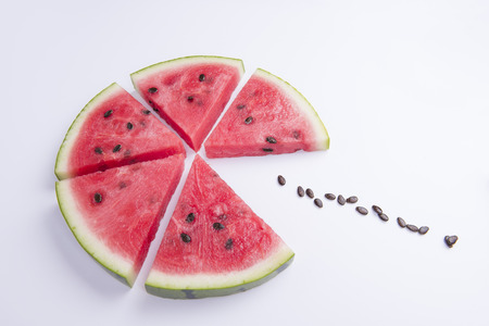 Creative photo of a watermelon slice with seeds on white background. Stock fotó