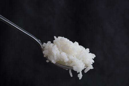 Scooping white rice with a spoon on dark background