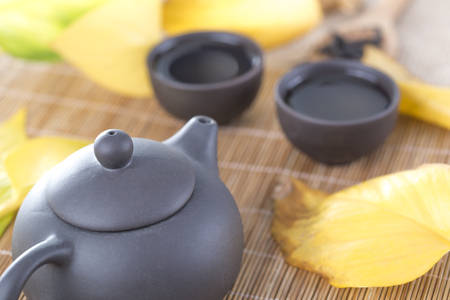 Black teapot and cups with yellow leaves on the table. Hot drinks. Autumn tea.