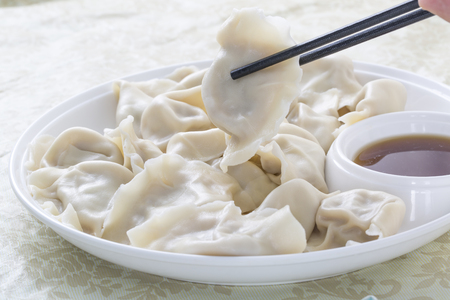 Close-Up Of Chinese Dumplings With Chopsticks.
