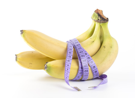 Healthy Eating - Concept photograph of banana with measurement tape on white background.