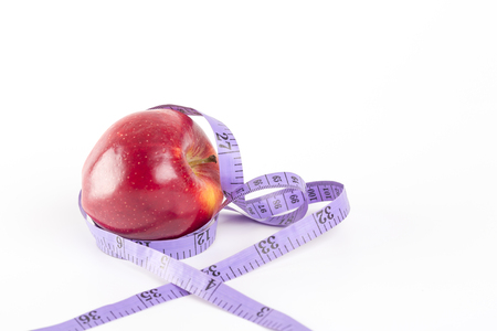 Measurement tape wrapped around red apple. Concept for health, diet