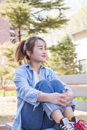 Young woman sitting on bench in university 版權商用圖片