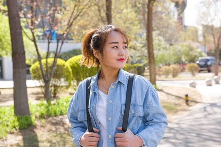 Female student walking in campus Standard-Bild