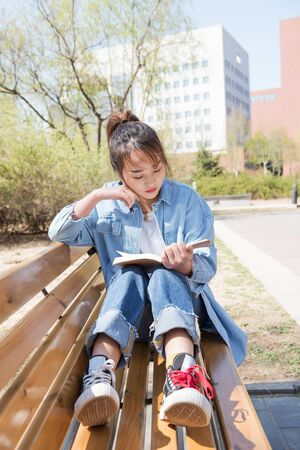 Young woman sitting on bench in park, reading book on a sunny day.