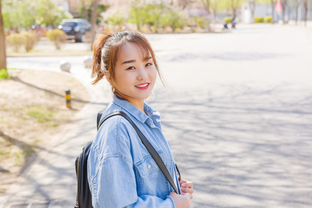 Portrait of Asian college student at campus. Female student walking to class on campus