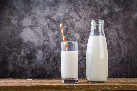 Glass of milk with straw and milk bottle on wooden table 写真素材