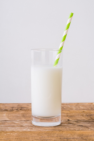 Glass of milk with straw on wooden table 写真素材