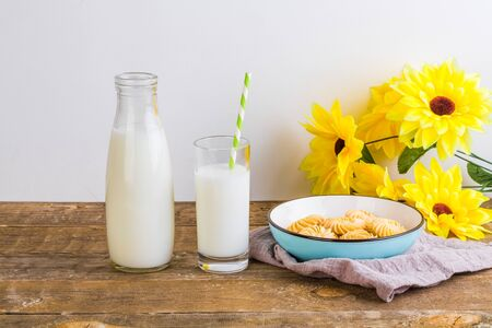 A glass of milk with milk bottle and cookies on wooden table