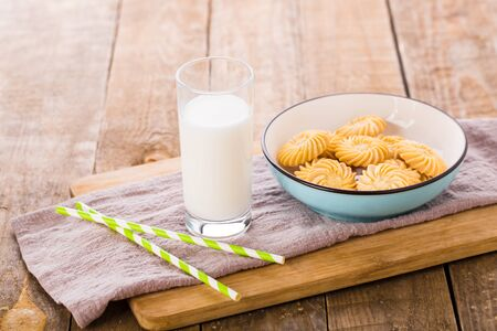 A glass of milk with straws and cookies